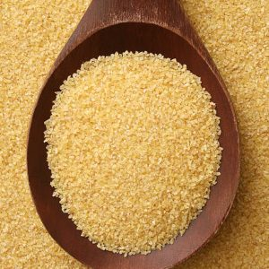 Top View Of Wooden Spoon Full Of Semolina Wheat Used To Prepare Couscous